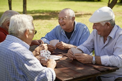 a group of male seniors sitting outside at a picnic table playing cards